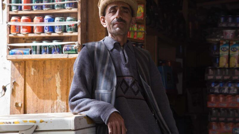 An Afghan shopkeeper in Ishkishim poses proudly in front of his shop.