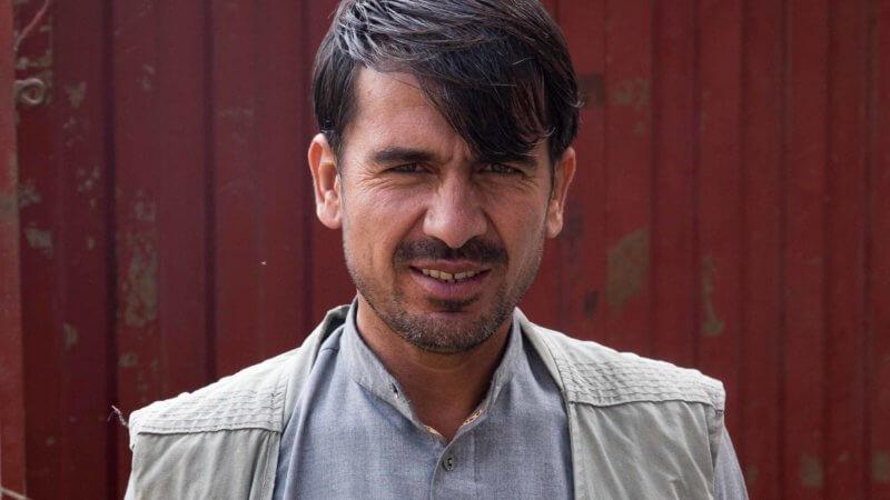 Afghan shopkeeper wearing white waistcoat.