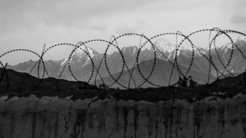 The Hindu Kush mountains framed through circles of barbed wire.