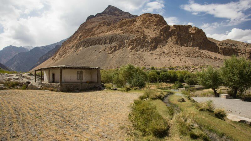 A house and rocky mountain valley leading to Pakistan's border.