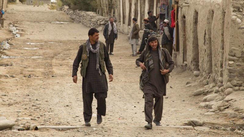 Two men walking down a dusty and quiet street in Khandud, Wakhan.