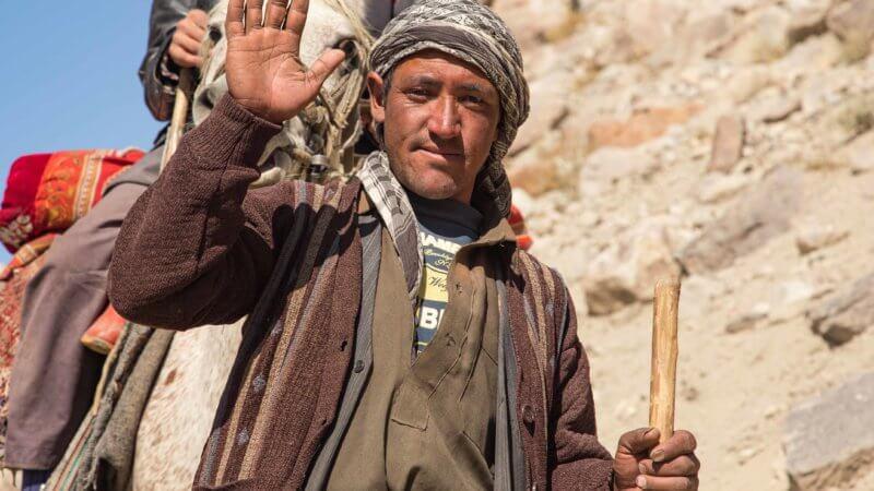 Wakhi herder man holding walking stick waves for the camera.