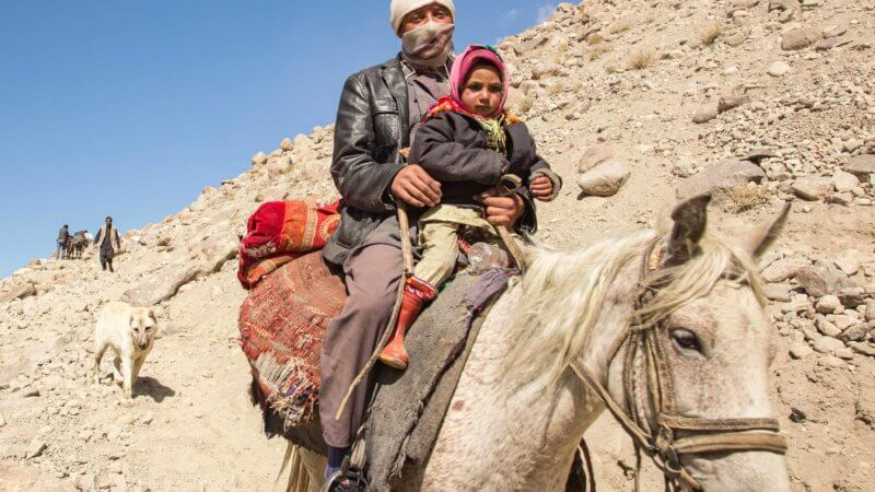A man riding downhill with his white horse and child on the front.