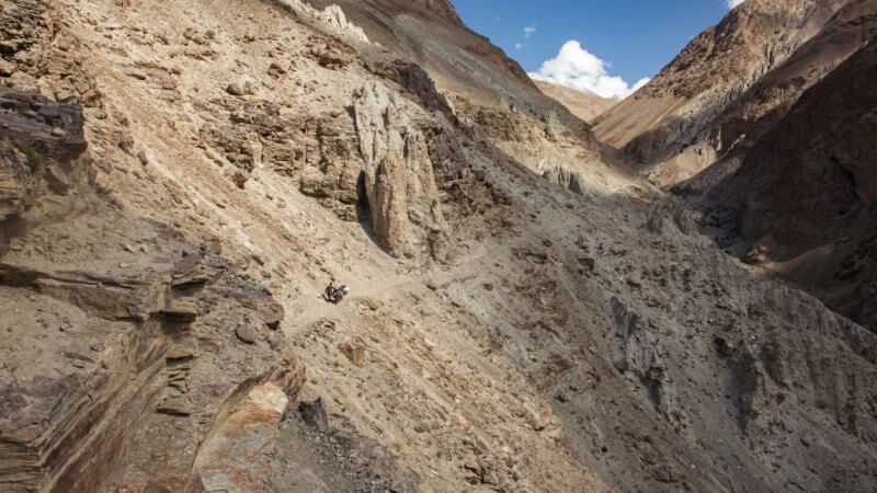 Looking into a Wakhan valley with a donkey herder far in the distance on a mountain trail.