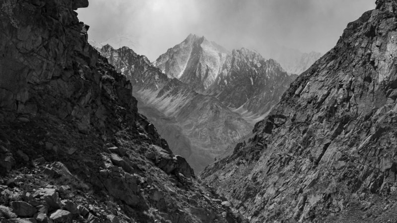 Black and white photo of 5,000m covered in a snow storm, surrounded by valley walls.