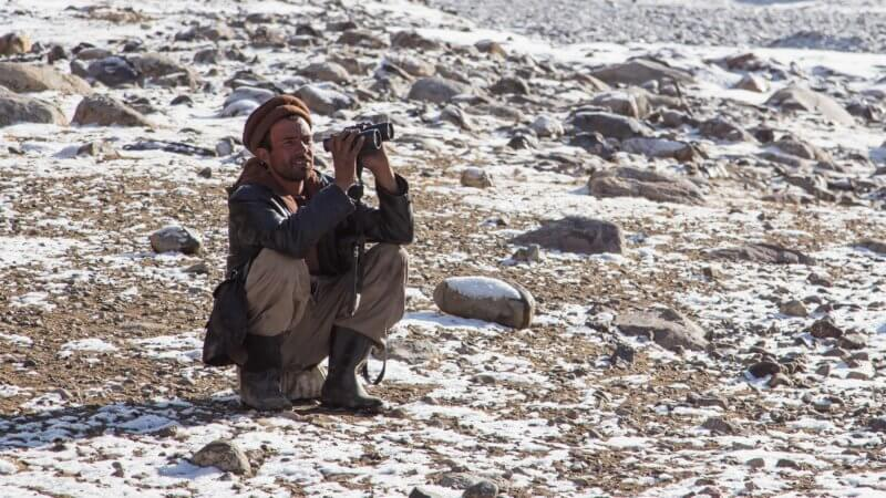 Afghan man wearing pakol hat, crouching down and looking through binoculars.