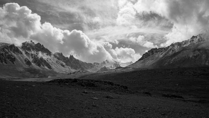 Black and white wide landscape photo of big clouds and a remote valley in distance.