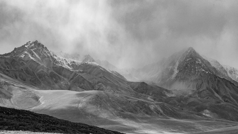 Black and white ethereal looking photo of a distant snow storm covering far away mountains.