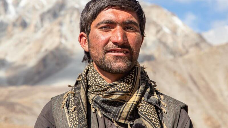 Shkor, a Wakhan herder and guide poses for a portrait and wearing a pretty scarf.