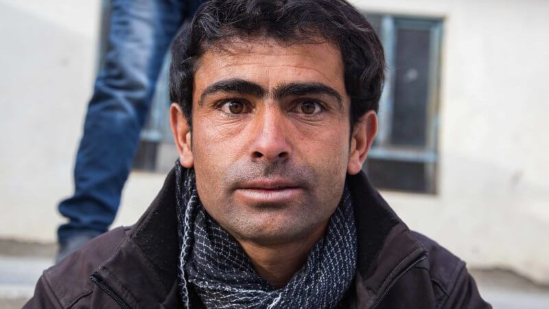 A man wearing a black coat and grey scarf stares into the camera lens.
