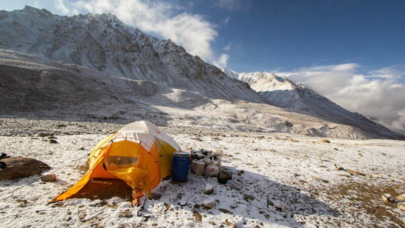 A yellow tent covered in a light dusting of snow in the Afghan mountains.