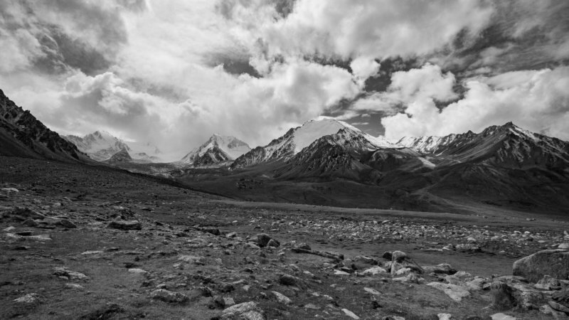 Black and white photo of Wakhan Corridor with snowy mountains and clouds in the distance.