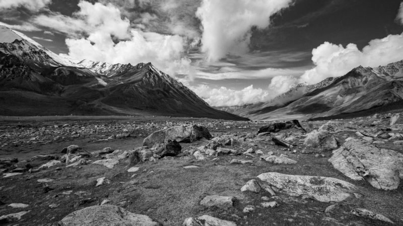 Black and white Wakhan Corridor photo of a wide valley with rocks.