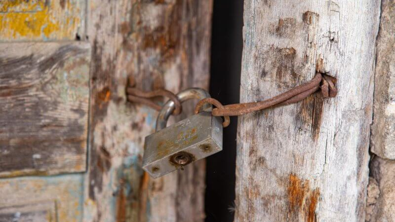 Close-up photo of an abandoned hut with a lock on the door.
