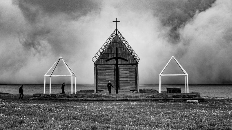 Three men approach a cross to pray, near the shores of misty lake in southern Georgia.