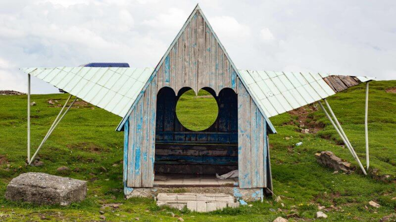 A steep roofed bus shelter in a mountain village in southern Georgia.