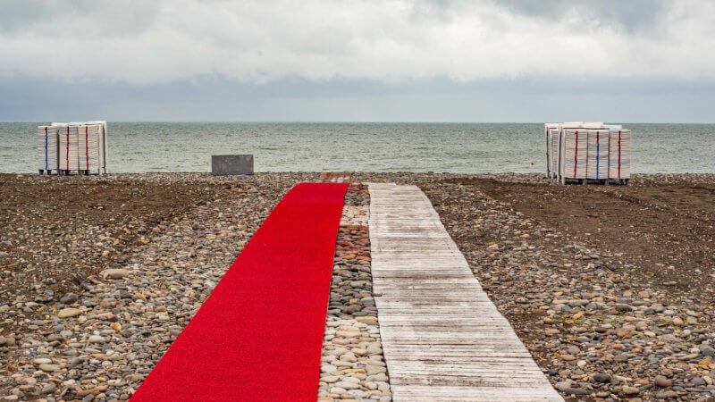 Red and white carpeted walkway extends out across shingle beach in Batumi, leading towards the Black Sea.