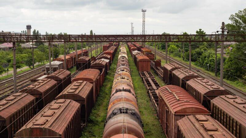 Rows of disused and rusting train carriages sit at a train station.