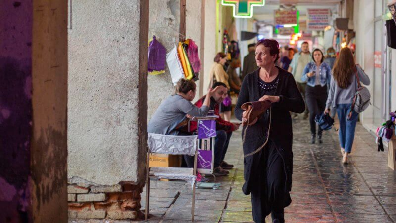 An older woman with a black gown clutches her purse as she walks past a covered market in Kutaisi, Georgia.