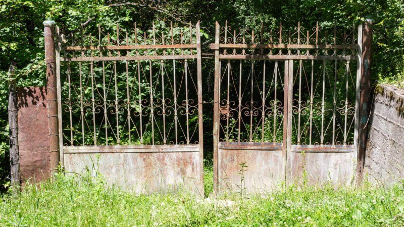 A rusted brown metal fence in a Georgian village guards an overgrown garden.