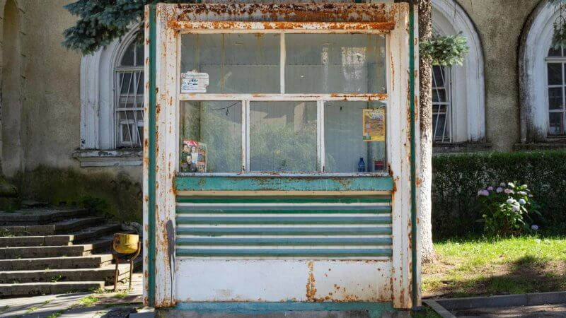 A rusted white and green coloured booth plastered in a few flyers.