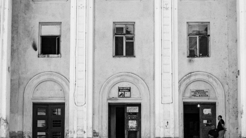 Black and white photo of an old theatre building in Georgia with three doors and two men stood outside.