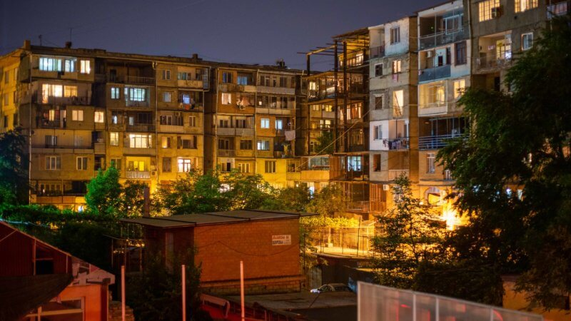 Night time photo of Tbilisi, Georgia housing estate blocks with dozens of apartment lights turned on.