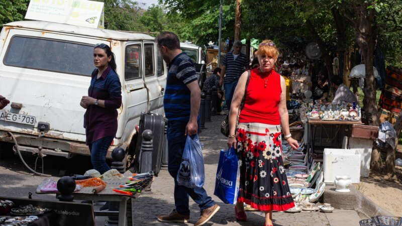 A red haired woman wearing a flowery skirt and red top walks through a flea market in Tbilisi.