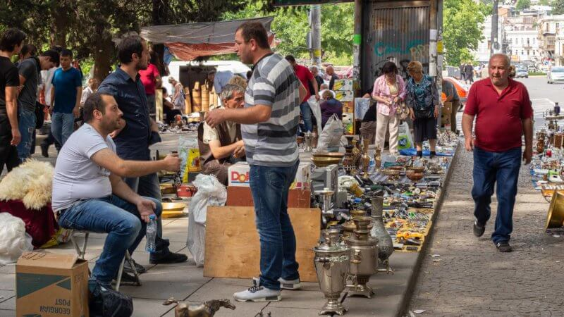 A flea market in Tbilisi with vendors chatting next to their tea pots for sale.