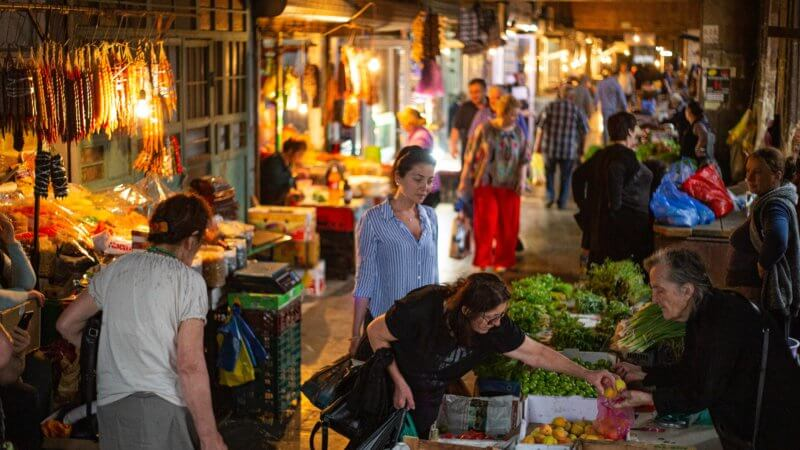 Shoppers in a covered market in Kutaisi shop for fruit and vegetables.