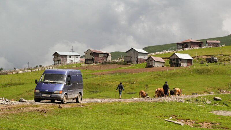A blue van in the mountains, with rugged-looking huts in the background and boys herding cows.