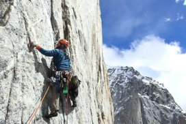 A rock climber with equipment climbs up a steep granite rock face in Pakistan.