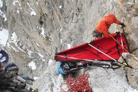 GoPro footage screenshot of Max Fisher assembling a portaledge somewhere on a rocky Pakistani cliff face.