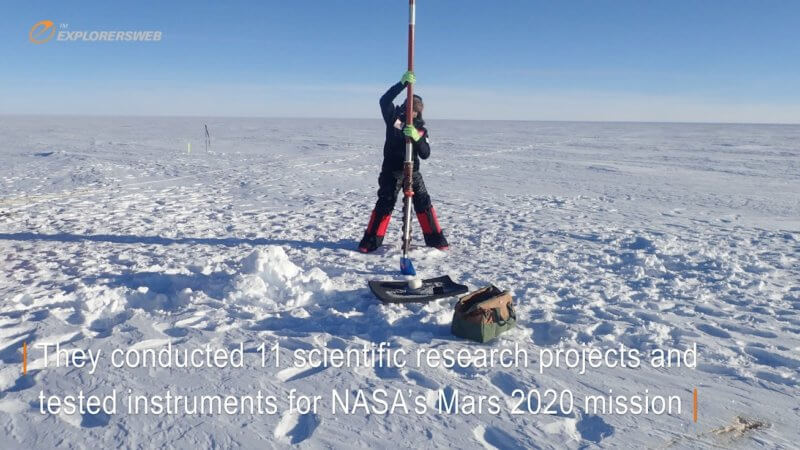 A Spanish scientist pulls out a very long core sample from the Antarctic ice sheet.