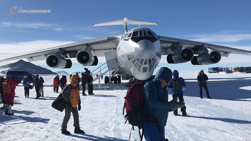 A Soviet-era plane on the Ice Runway in Antarctica, with multiple tourists wandering around outside.