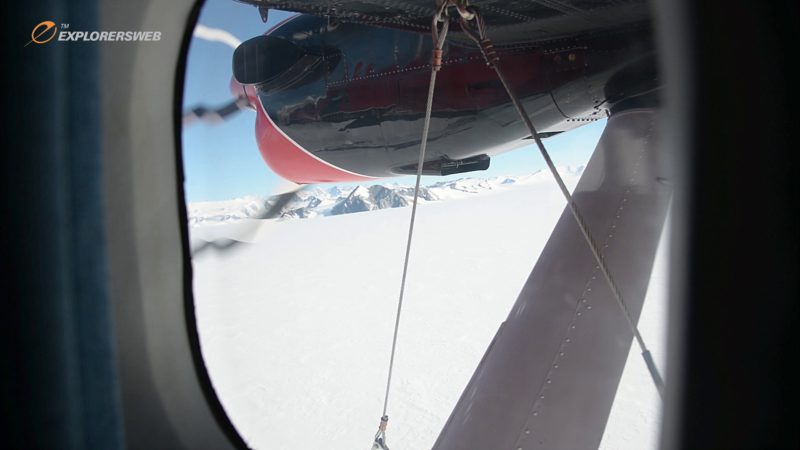Looking through the window of a propeller plane flying over the icy expanse of Antarctica.