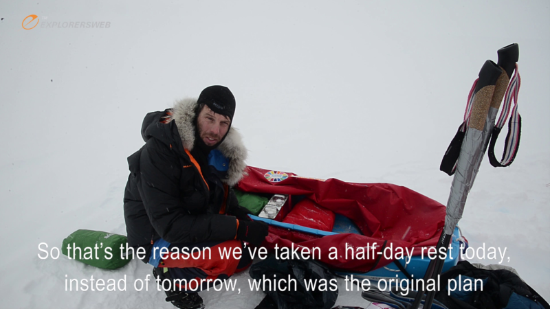 Antarctic explorer crouched down next to his unpacked sled.