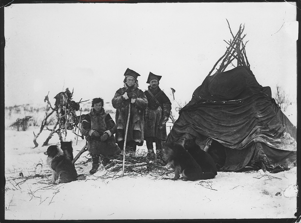 Historical photo of three Sami and their dogs stood next to their lavvu traditional wooden tent.