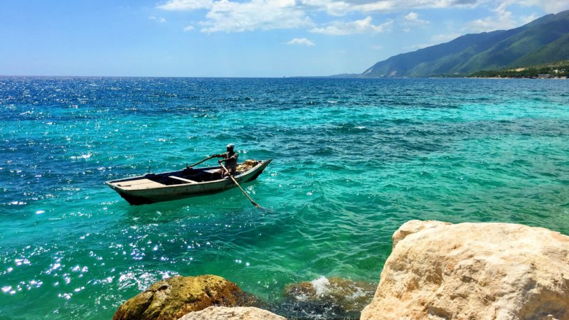 A Haitian man rows a wooden boat across emerald green seas.