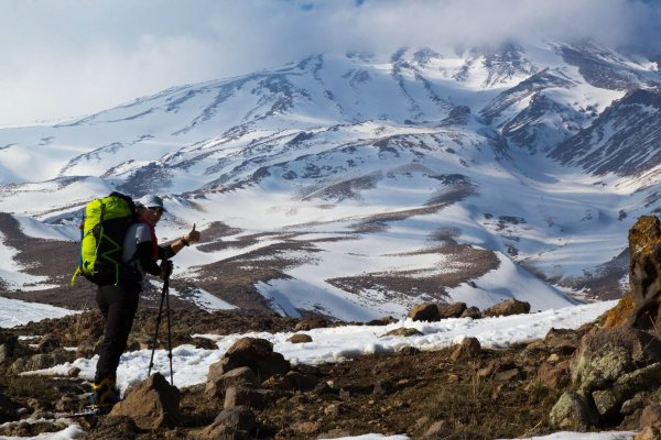 Shirin gives a smile and thumbs up during her ascent. A photo of Mount Damavand's summit is in the background, covered in mist.