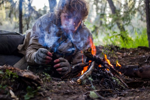 A close up photo of an adventure huddled in the dirt and making a fire.
