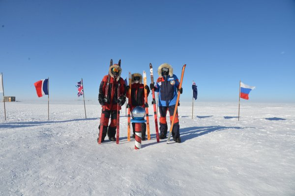 Ryan Waters and two of his teammates pose for a photo, holding their skis, by the South Pole marker.