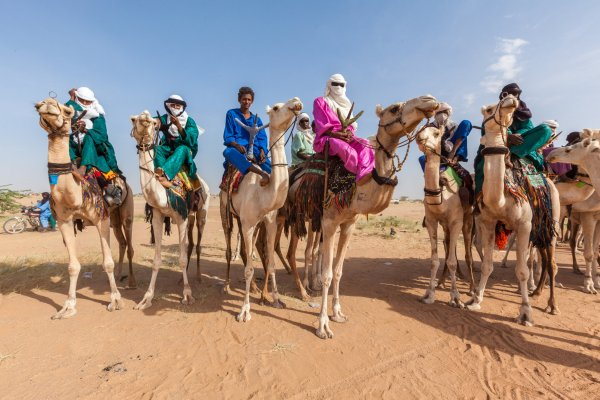 A group of Tuaregs on white camels, wearing colorful clothing and headscarves in an orange sandy desert.